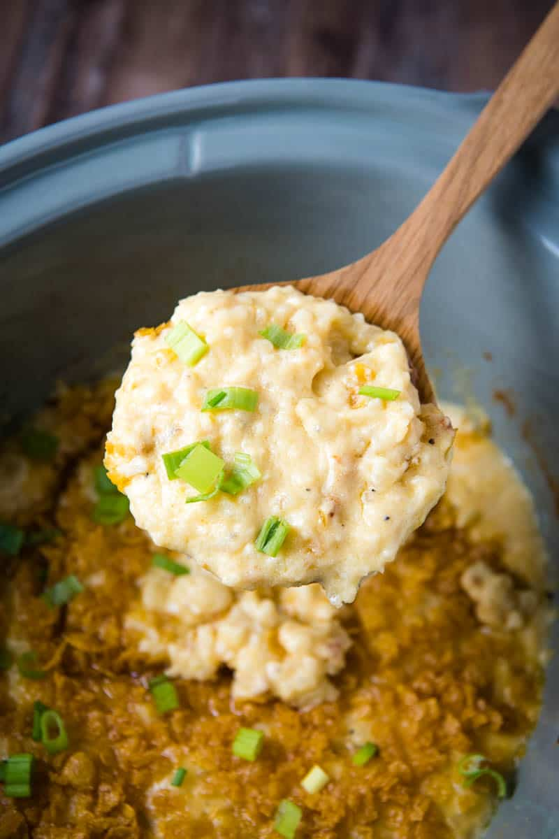 serving of slow cooker funeral potatoes, sprinkled with green onions, on wooden spoon over CrockPot