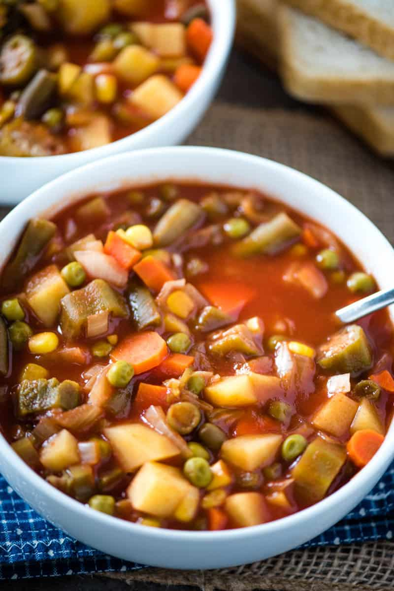 white bowl full of slow cooker V8 vegetable soup with spoon
