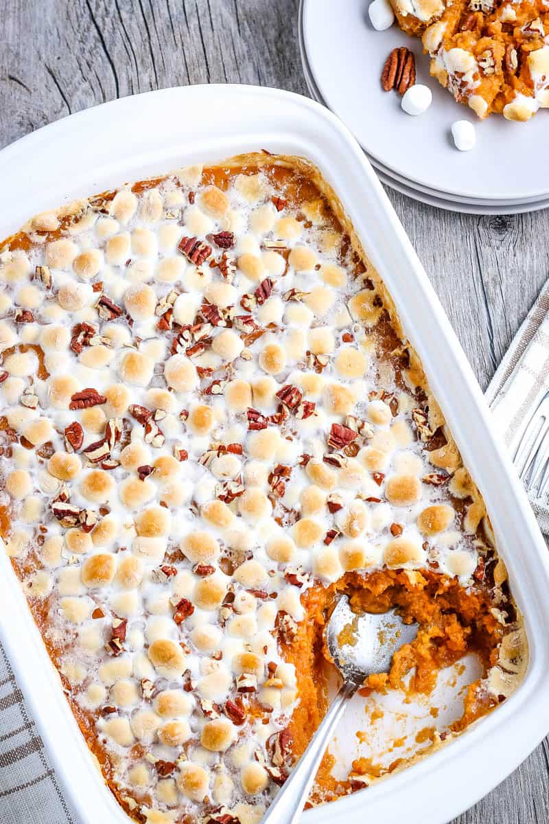 spoon scooping southern sweet potato casserole out of white baking dish and onto small white plate