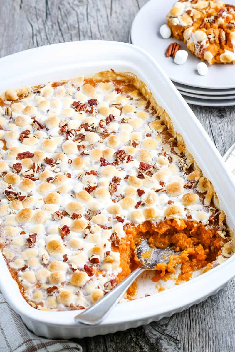 spoon in sweet potato casserole in white baking dish