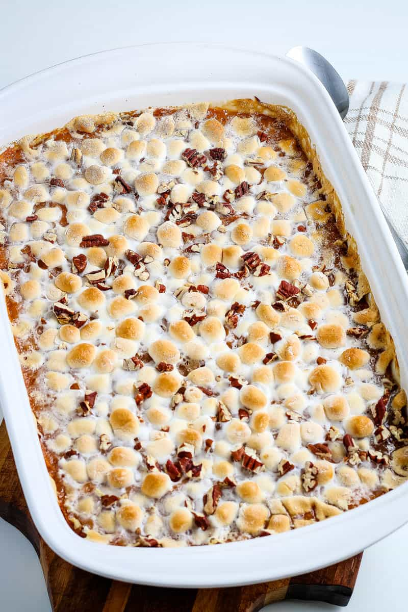 baked sweet potato casserole with marshmallows and pecans in white casserole dish