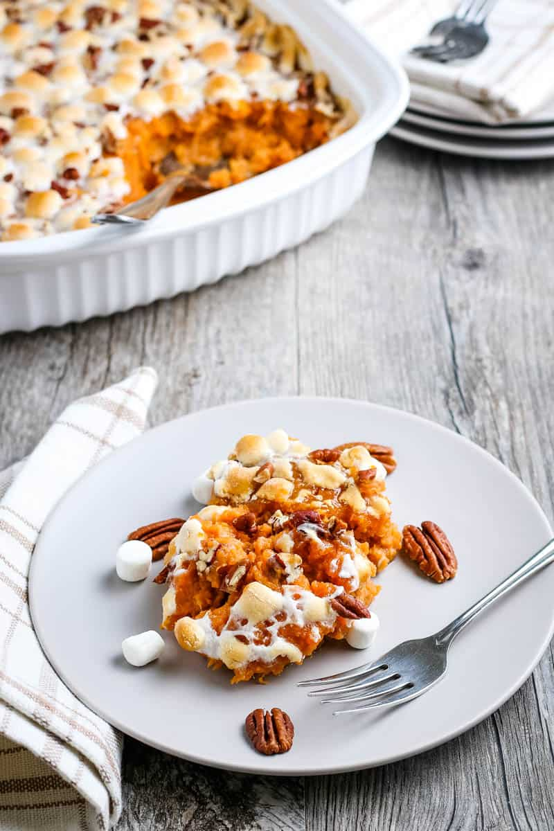 serving of sweet potato and marshmallow casserole on gray plate with fork