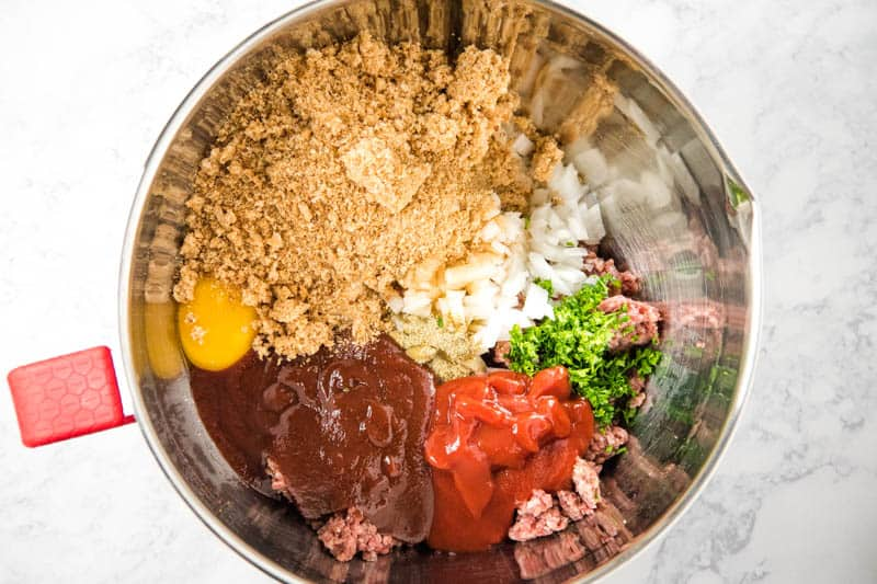 traditional meatloaf ingredients, including ground beef, eggs, onion, garlic, parsley, seasoned salt, ketchup, bbq sauce, and bread crumbs in metal mixing bowl