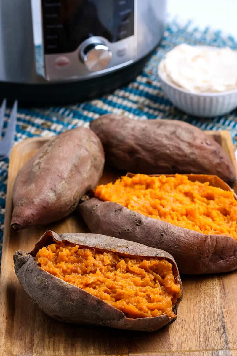 steamed sweet potatoes cooked in the Instant Pot, sitting on wooden cutting board and sliced open