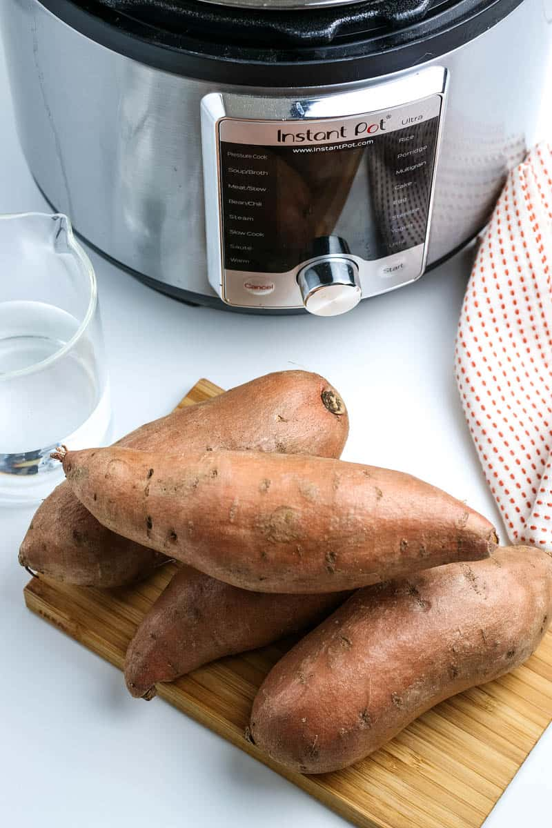 ingredients for Instant Pot sweet potatoes, including sweet potatoes on a wooden cutting board, water, and an Instant Pot