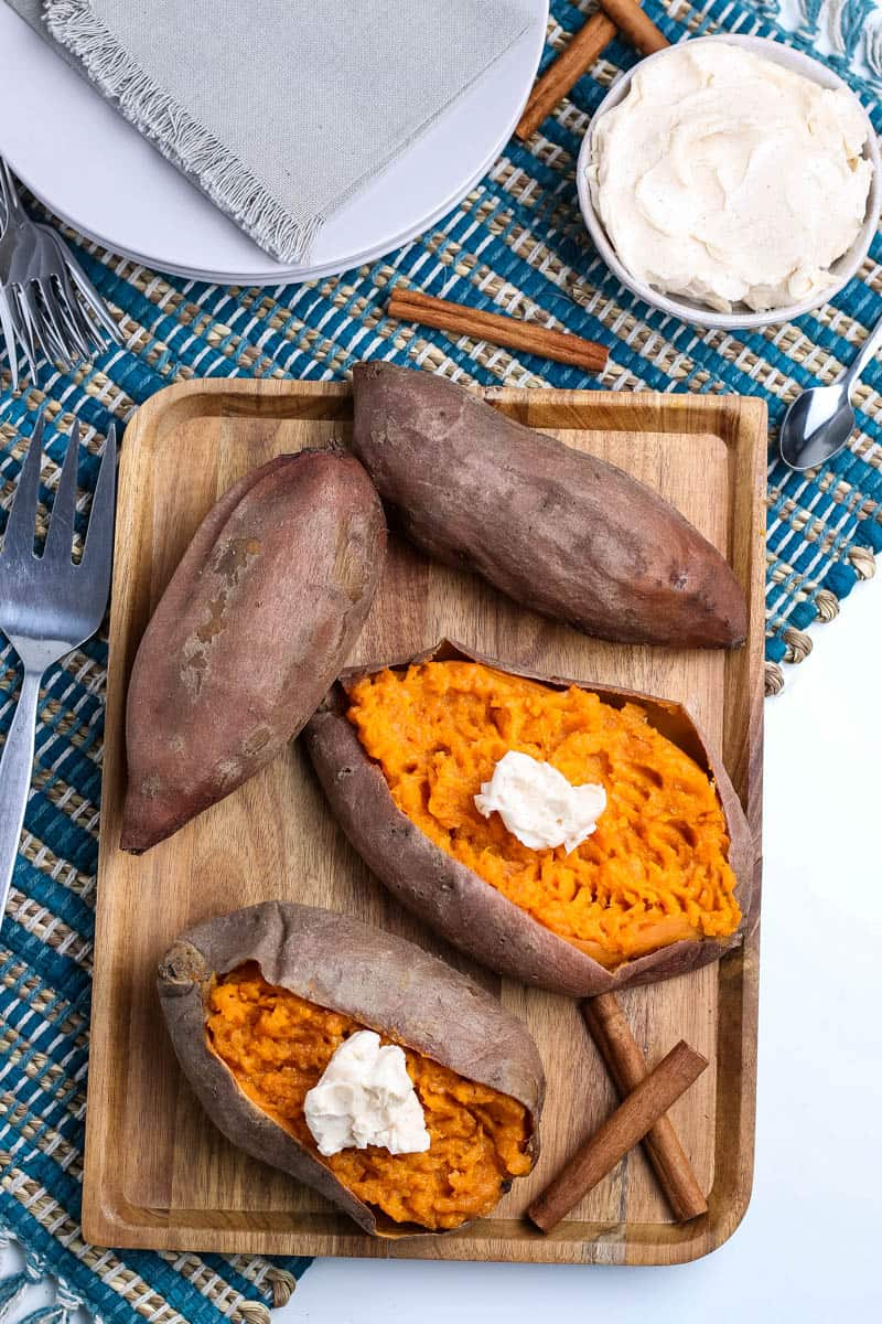 pressure cooked sweet potatoes on wooden cutting board with cinnamon sticks, on blue woven placemat with white plates, fork, spoon, and small bowl of whipped cinnamon butter