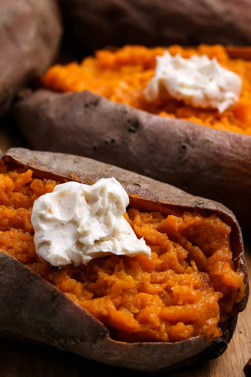 Instant Pot sweet potatoes sliced open on cutting board with dollop of whipped cinnamon butter