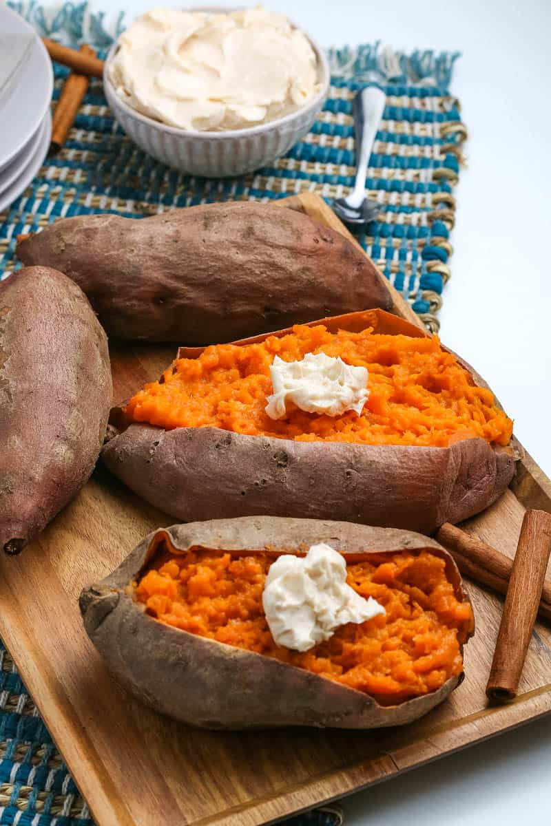 pressure cooker sweet potatoes topped with whipped cinnamon butter on wooden cutting board with cinnamon sticks and blue woven placemat
