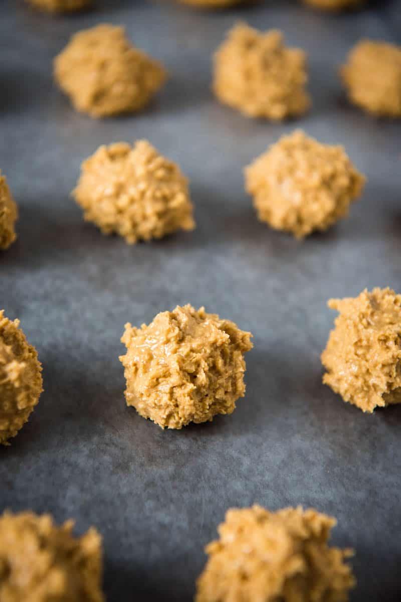 rolled crispy peanut butter balls on wax paper lined baking sheet