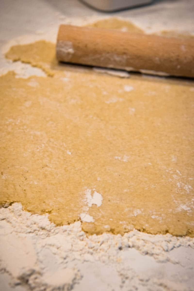 rolled sugar cookies dough on floured surface with rolling pin