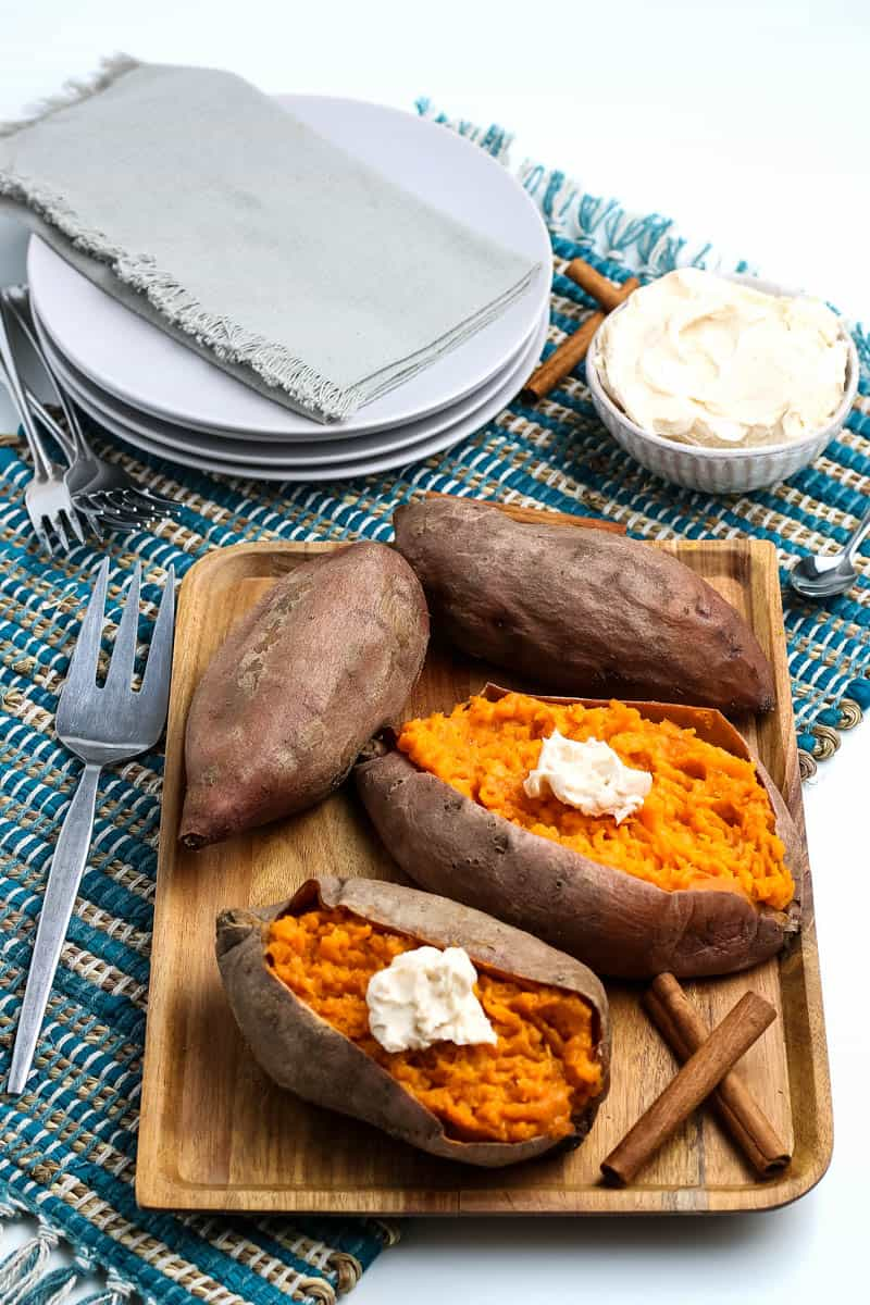 steamed sweet potatoes and whole sweet potatoes sitting on wooden tray with cinnamon sticks and woven blue placemat