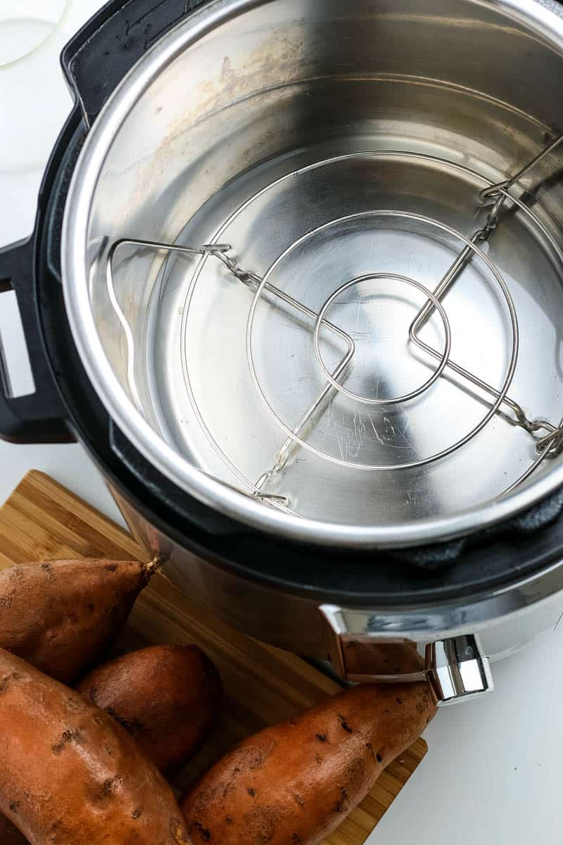 water and steaming trivet in Instant Pot with sweet potatoes on wooden cutting board