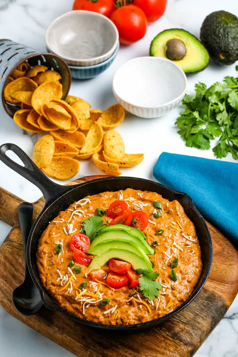 skillet full of chili cream cheese dip, topped with fresh avocado and tomatoes, served with corn chips, on wooden cutting board, on white marble countertop