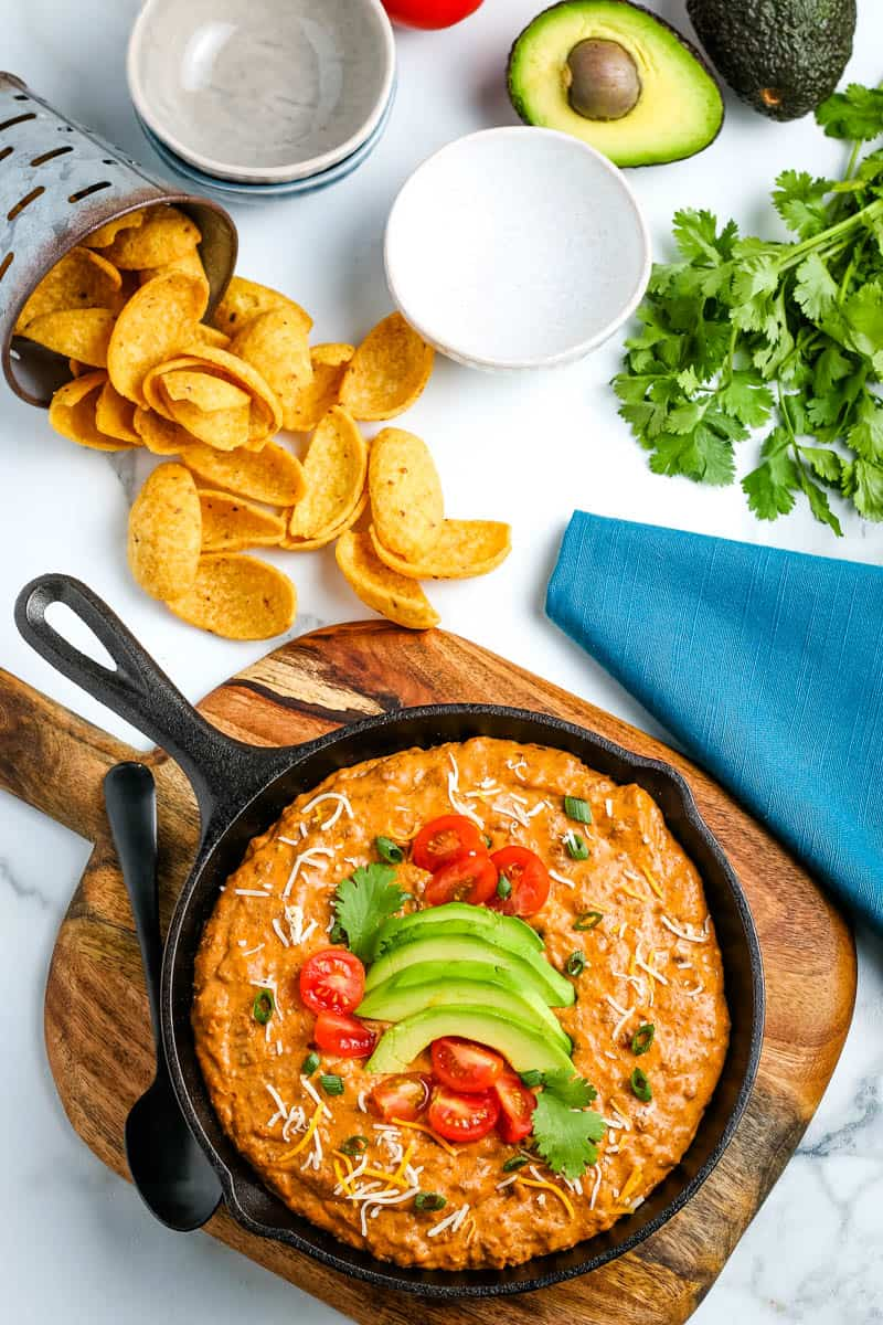 above cast iron skillet filled with Hormel chili cheese dip, topped with fresh tomatoes and avocado, served with corn chips, on wooden cutting board on white marble countertop