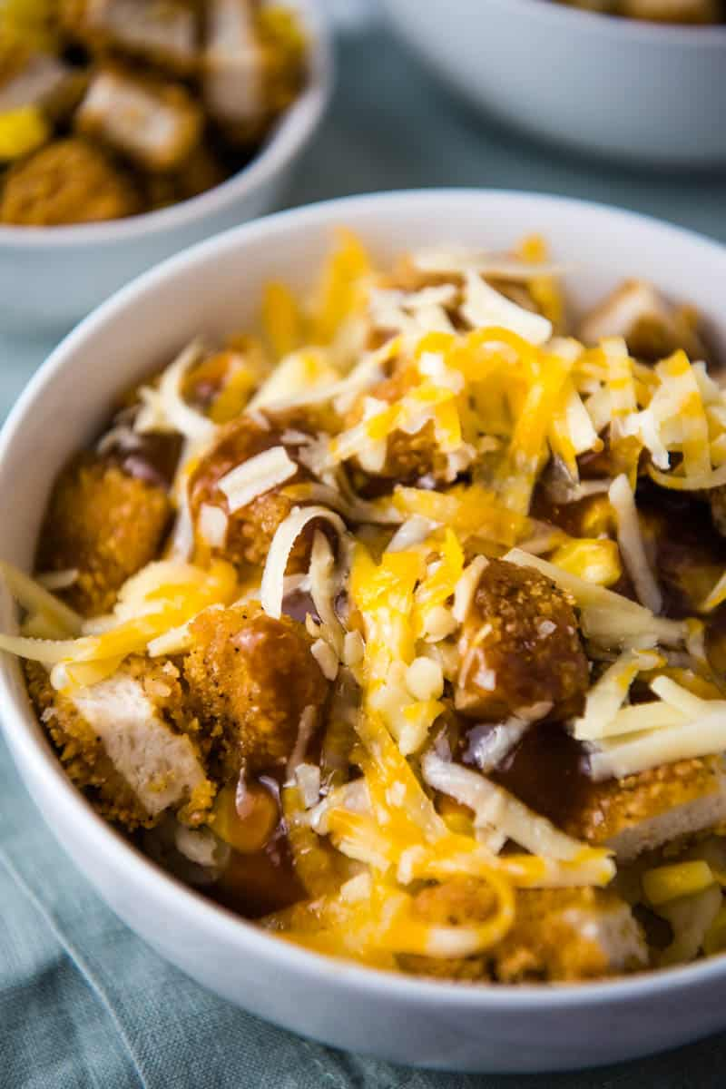 KFC Famous bowl ingredients, including mashed potatoes, corn, crispy chicken nuggets, brown gravy, and shredded cheese in white bowl