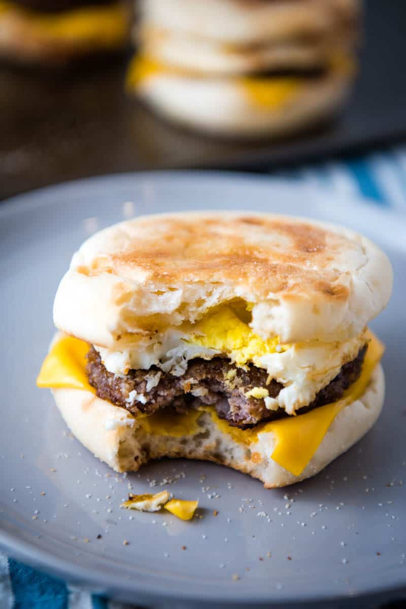 bite out of sausage egg and cheese McMuffin on gray plate