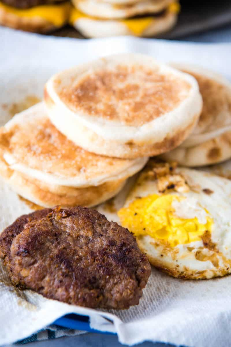 sausage McMuffin ingredients, including English muffins, sausage patties, and eggs on blue plate with paper towel