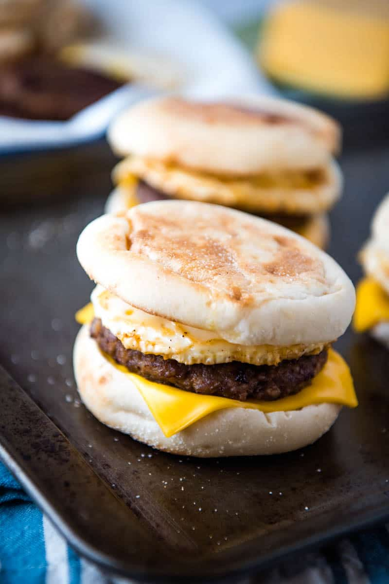 sausage and egg McMuffin sandwich on baking sheet with more breakfast sandwiches