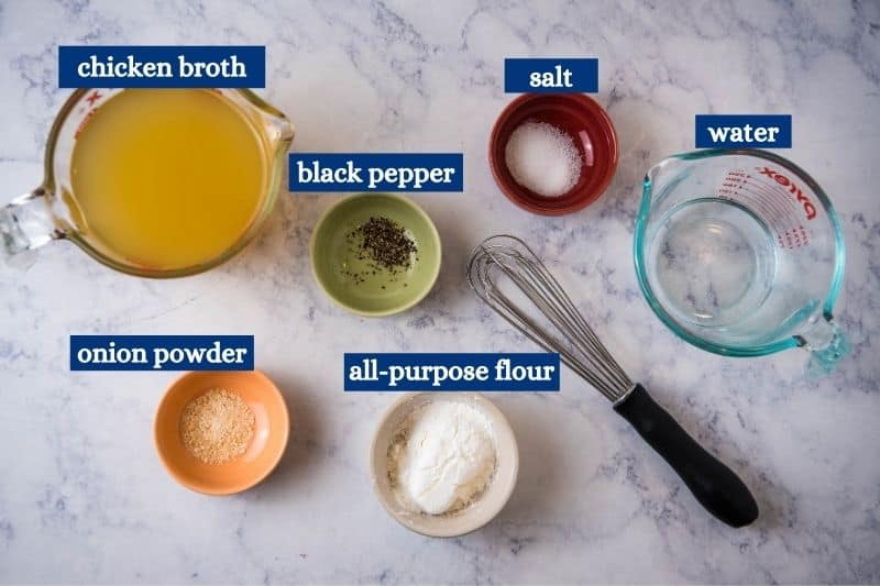 chicken gravy ingredients, including chicken broth, black pepper, salt, water, onion powder, and all-purpose flour on white marble countertop with black whisk