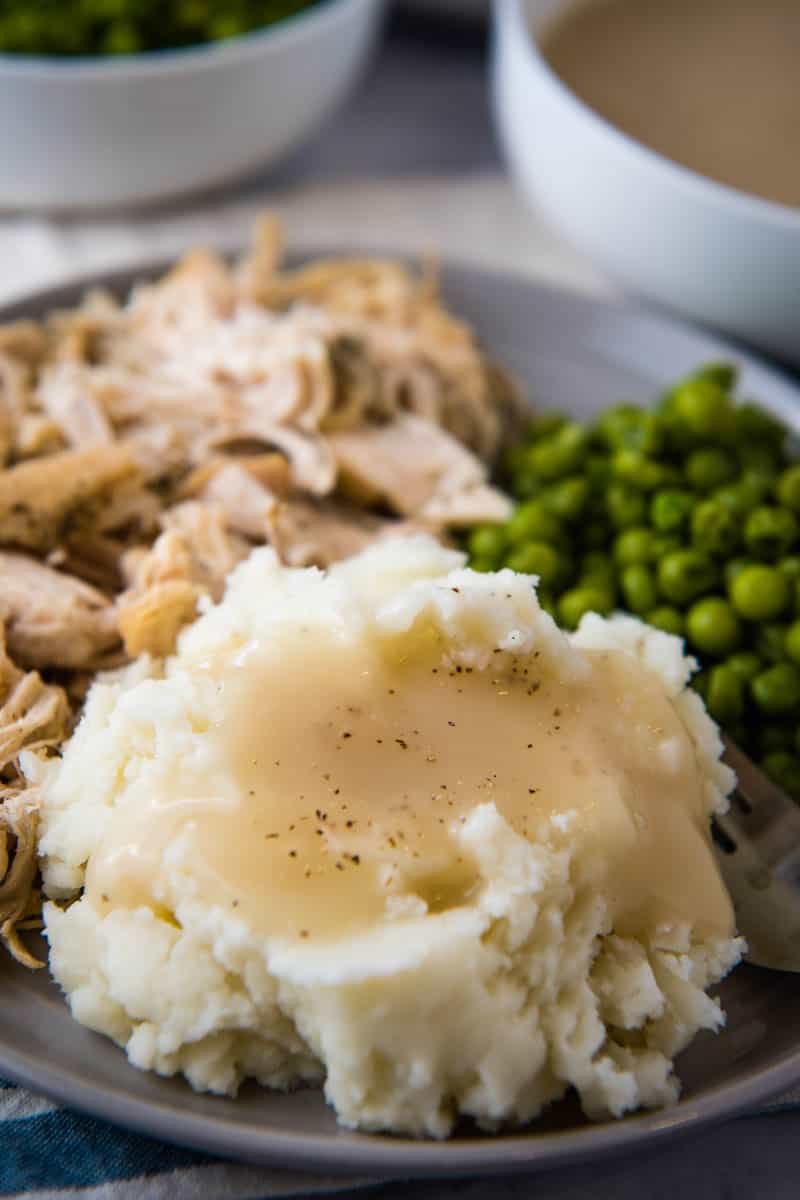 chicken gravy poured over mashed potatoes on gray plate with shredded chicken and green peas