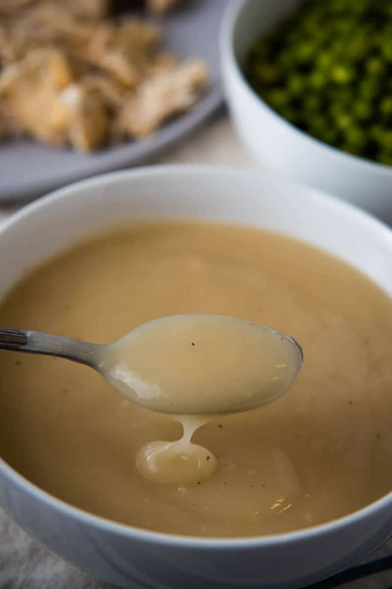 spoonful of easy chicken gravy over white bowl full of gravy