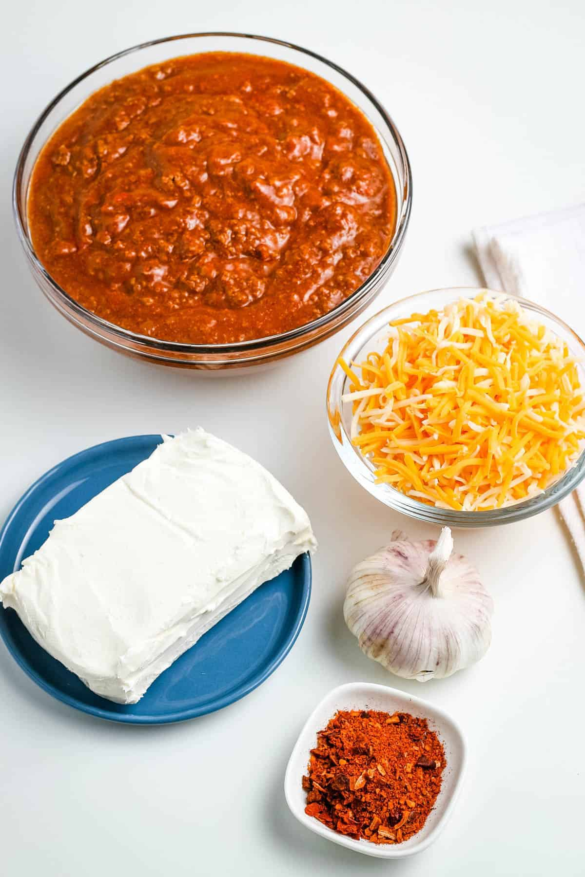 ingredients for chili dip in glass bowls, including chili without beans, shredded cheese, cream cheese, garlic, and taco seasoning