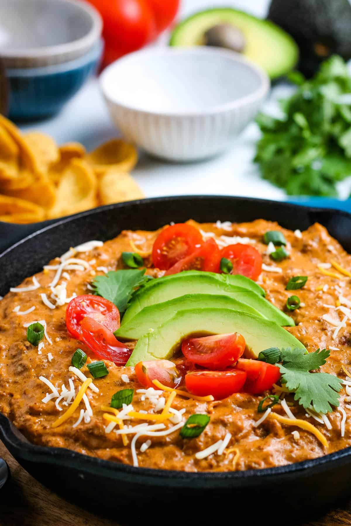 close up of chili dip, topped with sliced avocado, cilantro, and fresh diced tomatoes, in cast iron skillet