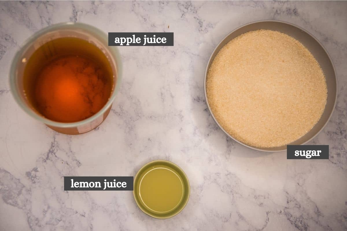 3 ingredients for apple jelly recipe, including apple juice, lemon juice, and sugar on white marble countertop