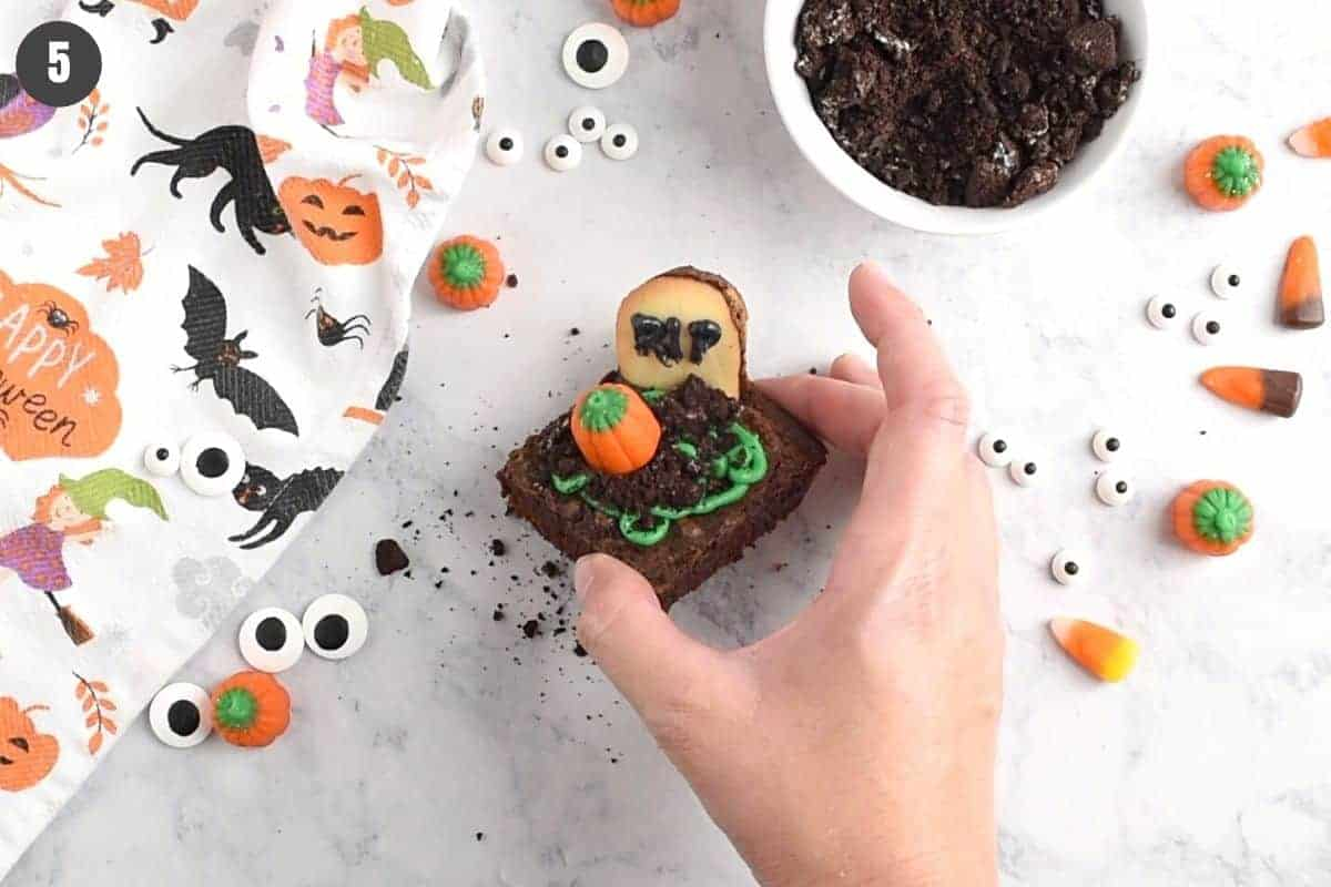 hand holding finished Halloween graveyard brownie with candy pumpkin on top
